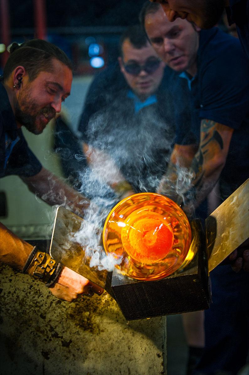 Photo d'un groupe d'hommes qui travaillent du verre en fusion