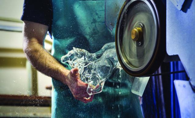 bras qui tiennent une stuae de chevaux en cristal en train de les tailler